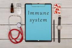presse-papiers avec le texte et le x22 ; System& immunisé x22 ; , pilules, stéthoscope et montre images stock