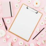 Presse-papiers, carnet et stylo avec les roses blanches sur le fond rose Configuration plate, vue supérieure Concept d'affaires Images libres de droits