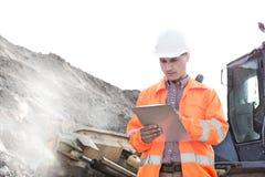 Presse-papiers de lecture d'ingénieur au chantier de construction Photographie stock