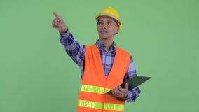 Presse-papiers de participation de travailleur de la construction d'homme et doigt ethniques multi heureux de pointage banque de vidéos