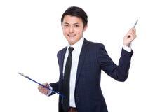Presse-papiers de prise d'homme d'affaires et plume asiatiques  Image stock