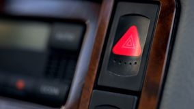 Pressed and glowing emergency car hazard warning flasher button on dashboard. Stock photo stock image