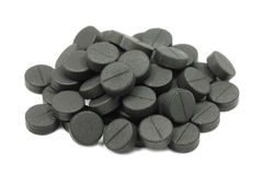 The pressed pills of activated carbon. On a white background stock image