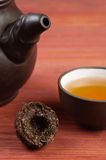 Pressed pu erh tea leaves briquette with clay glazed teabowl and part of clay teapot on red wooden table Stock Photos