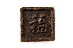 Pressed tea, hieroglyph. A square block of black chinese pressed tea pu-erh Royalty Free Stock Photography