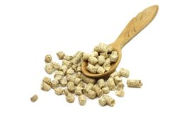 Pressed wooden pellets in a spoon. On a white background Stock Images