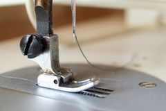 Presser foot of sewing machine. Threading the textile macro close up Royalty Free Stock Photography