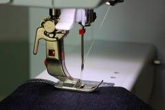 Presservoet van een naaimachine met donkere stof stock foto's