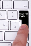 Pressing black button with pray for paris text and sign Stock Image