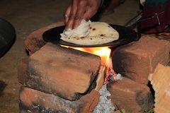 Pressing Bread to Make a Air in Roti on Tawa. Image of making roti bread in rural area in indian village in traditional style .Cooking in night time stock photo