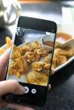 Pressing de doigt sur le smartphone pour la nourriture chinoise de photographie dans la recherche Photographie stock libre de droits
