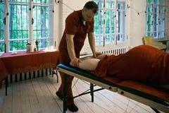 Pressing de thérapeute sur des jambes Images stock