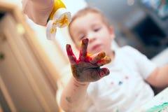 Pressing finger-paint on boys hand Stock Photos