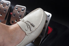Pressing gas pedal. Woman's foot pressing the gas pedal Royalty Free Stock Images