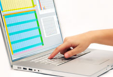Pressing a laptop key. Image shows a finger pressing a key on a contemporary laptop  displaying a business spreadsheet Stock Photos