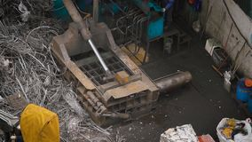 Pressing machine is compressing metal scrap in a wrecking yard of scrap processing plant, outdoors in daytime. Automatically old dirty pressing machine is stock video footage