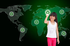 Pressing recycle icon. Little girl pressing recycle icon on world map Royalty Free Stock Images