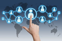 Pressing social media icon. Woman hand pressing social media icon on blue-white background with world map Stock Photos