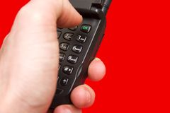 Pressing the telephone's OK button. A hand dialing a mobile phone on a red backround Royalty Free Stock Image