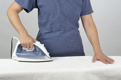 Pressing time. Woman standing and ironing a white tablecloth Stock Photography
