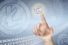 Pressing virtual litecoin sign. Female finger pressing virtual litecoin sign Stock Photo
