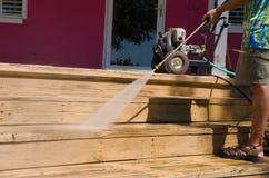 Pression d'homme de DIY lavant les escaliers en bois de plate-forme Photographie stock