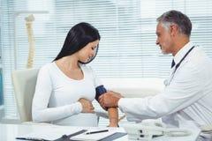 Pression de mesure de docteur de femme enceinte Image stock