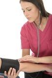 Pression femelle professionnelle intéressée de docteur Taking The Blood de jeunes d'un patient et de l'écoute avec le stéthoscope Images stock