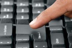 Pressionando a chave do entre no teclado de computador Fotos de Stock