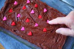 Pressionando corações dos doces no caramelo Foto de Stock