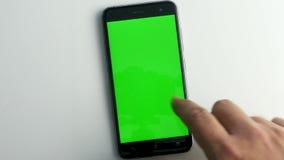 Pressionando o telefone esperto com a tela verde no branco vídeos de arquivo