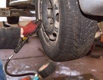 Pressione d'aria di misurazione sulle gomme di automobile dopo il cambiamento delle gomme fotografie stock libere da diritti