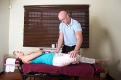 Pressione del chiropratico sui muscoli pazienti della gamba Fotografie Stock
