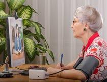 Pressione di misurazione durante il soggiorno virtuale di medico con Fotografia Stock