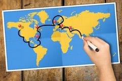 A pressione itinerario dell'indicatore della mano di viaggio della mappa di mondo Fotografie Stock Libere da Diritti