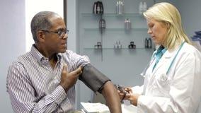 Pressione sanguigna del dottore Checking Male Patient stock footage