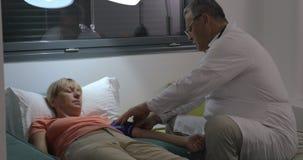 Pressione sanguigna di misurazione dei pazienti di medico maschio senior stock footage