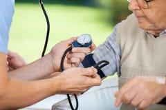 Pressione sanguigna di misurazione del guardiano maschio degli anziani fotografia stock libera da diritti