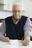 Pressione sanguigna di misurazione dell'uomo senior a casa fotografie stock libere da diritti