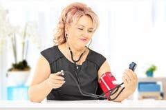 Pressione sanguigna di misurazione della donna invecchiata mezzo, a casa Immagine Stock