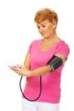 Pressione sanguigna di misurazione della donna senior con il manometro automatico immagini stock libere da diritti