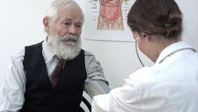 Pressione sanguigna di misurazione di medico del paziente maschio stock footage