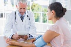 Pressione sanguigna di misurazione di medico di un paziente fotografia stock