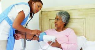 Pressione sanguigna di misurazione di medico femminile della donna senior in camera da letto 4k stock footage