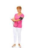 Pressione sanguigna di misurazione sorridente della donna senior Fotografia Stock