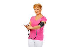 Pressione sanguigna di misurazione sorridente della donna senior Immagini Stock