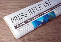 Pressmeddelande - tidning på skrivbordet i kontoret Arkivbild