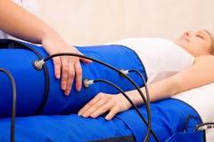 Pressotherapy maskin för ben på kvinna i skönhetmitt Royaltyfria Bilder