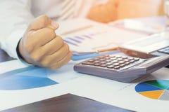 Pressung des Geschäftsmannes mit Papierdiagramm- und Finanzbeamter obje Stockfotografie
