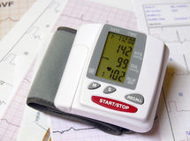 Pressure. Closeup of a blood pressure measuring device on top of ECG papers Royalty Free Stock Photos